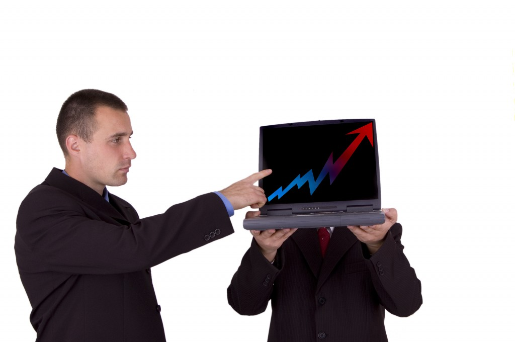 A man pointing at a computer screen showing the tracking of ppc traffic results.